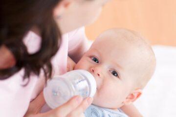 Reflux bij baby's baby drinkt fles in moeders armen