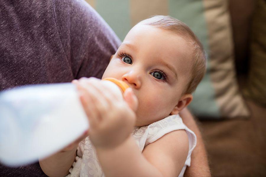baby met reflux drinkt melk uit flesje