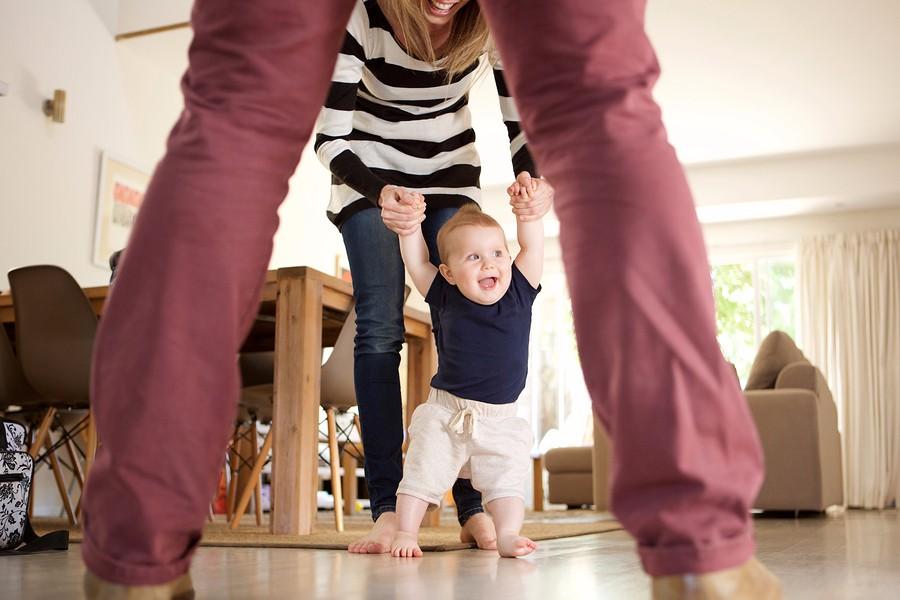baby zet zijn eerste stapjes en leert lopen