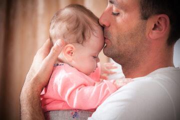 Vader houdt baby rechtop tegen zich aan om reflux te voorkomen