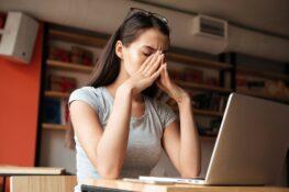 vrouw zit op het werk en heeft last van zwangerschapssymptomen