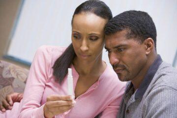 Man en vrouw kijken teleurgesteld naar zwangerschapstest bij verminderde vruchtbaarheid man