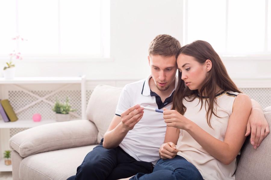Stel kijkt teleurgesteld naar zwangerschapstest bij verminderde vruchtbaarheid vrouw