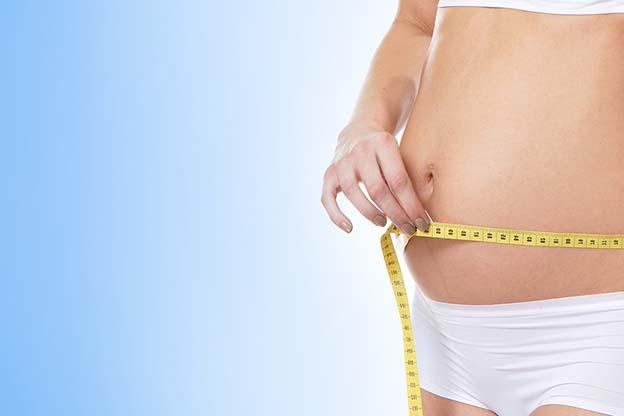 Vrouw meet omvang buik na 15 weken zwanger