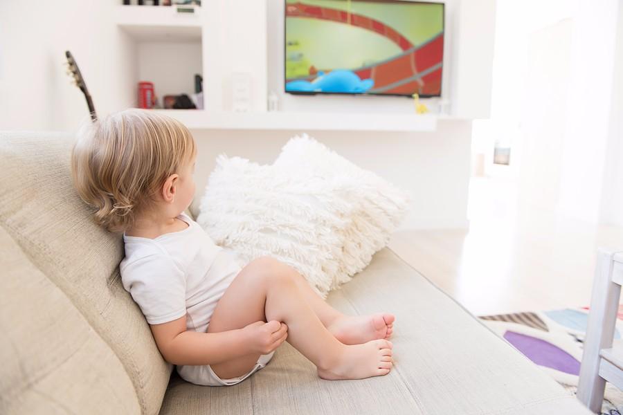 baby zit op de bank en kijkt tv
