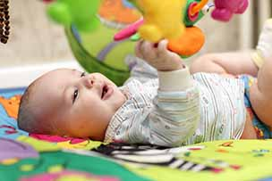 Baby van 4 maanden oud traint zijn oog-hand-coördinatie