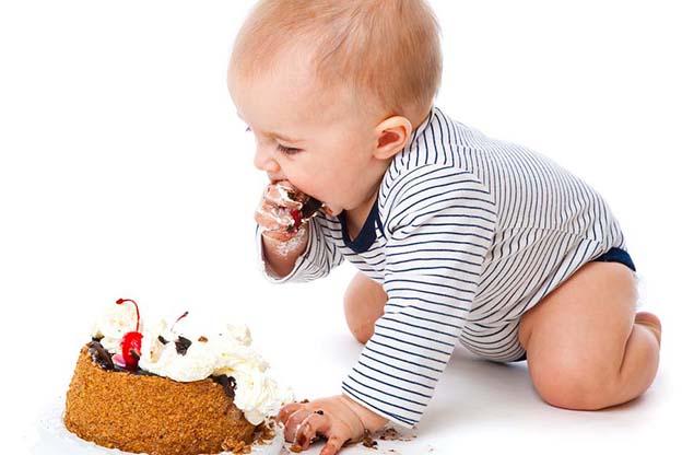 Een baby met een meptaart op zijn eerste verjaardag