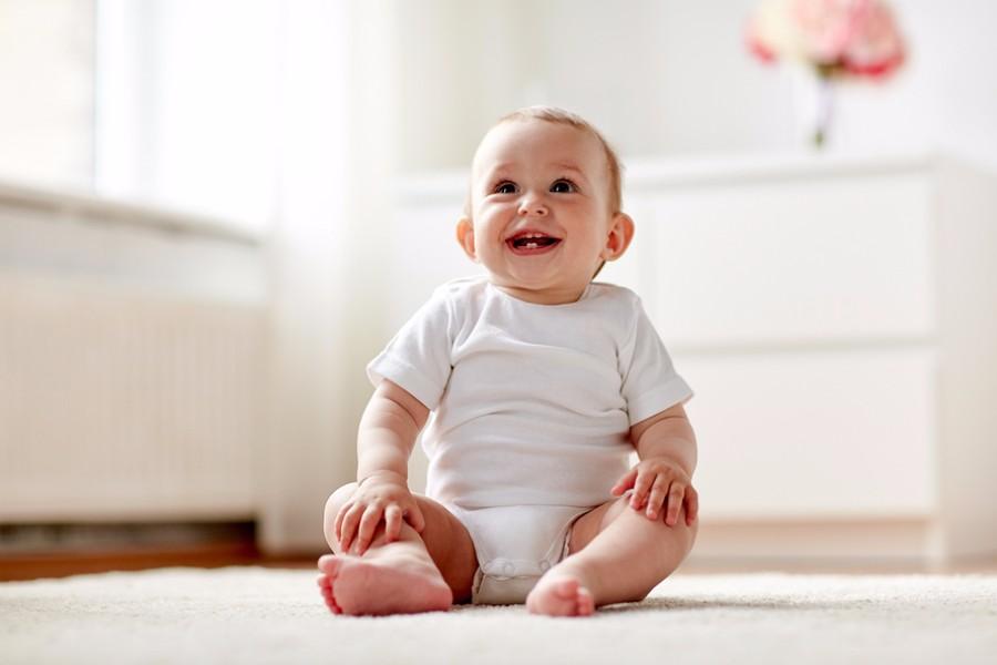 Baby 7 maanden oud, zit lachend rechtop