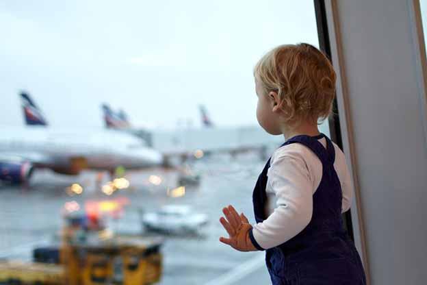 Peuter kijkt naar vliegtuig op vliegveld