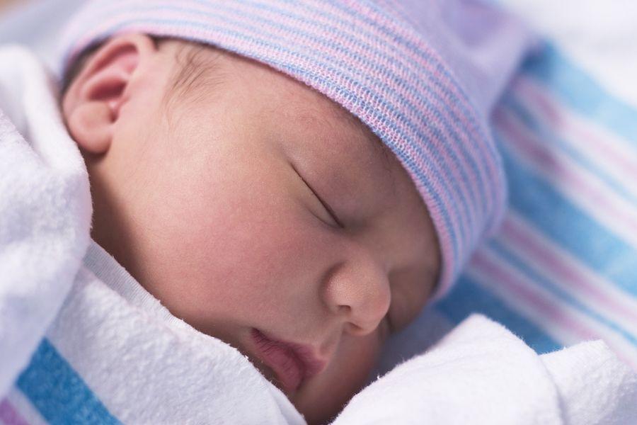 pasgeboren slaapt met babymutsje op