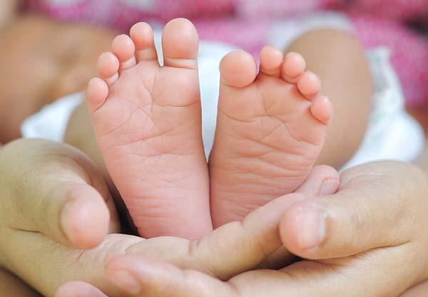 Babyvoetjes in de handen van haar moedern