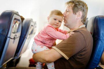 Vader probeert baby jetlag te verzachten van baby in vliegtuig