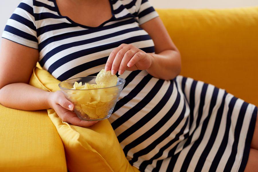 zwangere vrouw heeft last van vreetbuien en eet chips op de bank