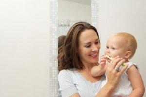 Tandenpoetsen baby - Een moeder poetst de tandje van haar baby.