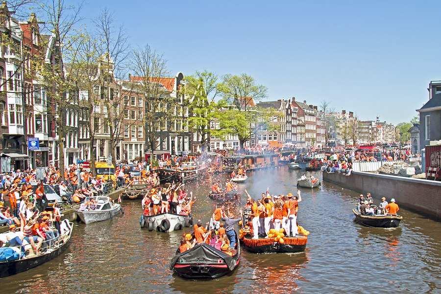 Viering Koningsdag op bootjes in de Amsterdamse grachten