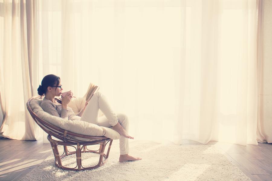 Vrouw leest boek en drinkt een kop thee
