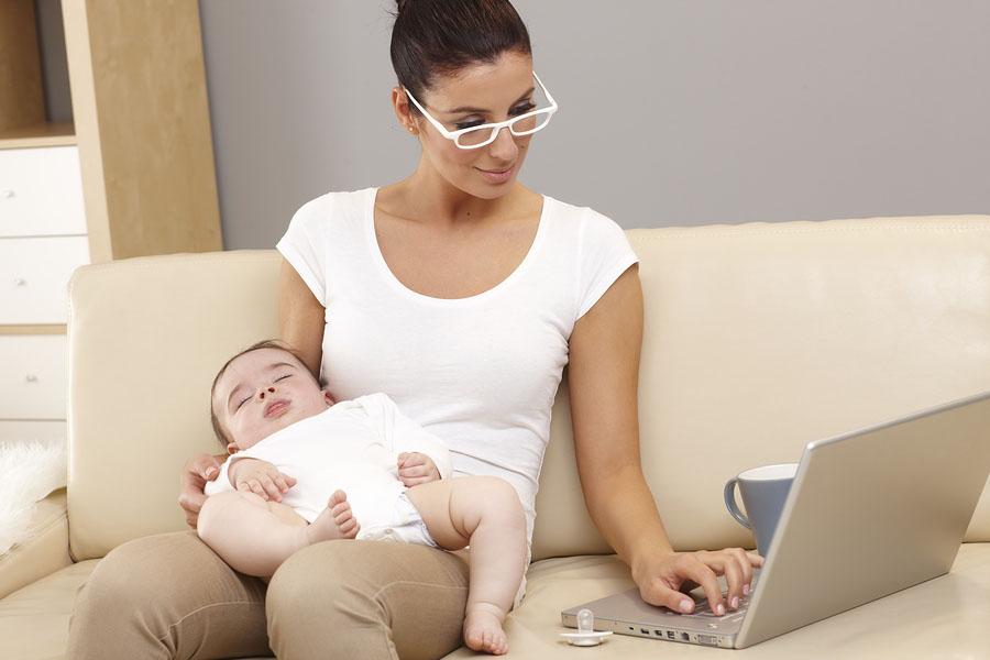 Vrouw bestelt online boodschappen achter laptop met baby op schoot