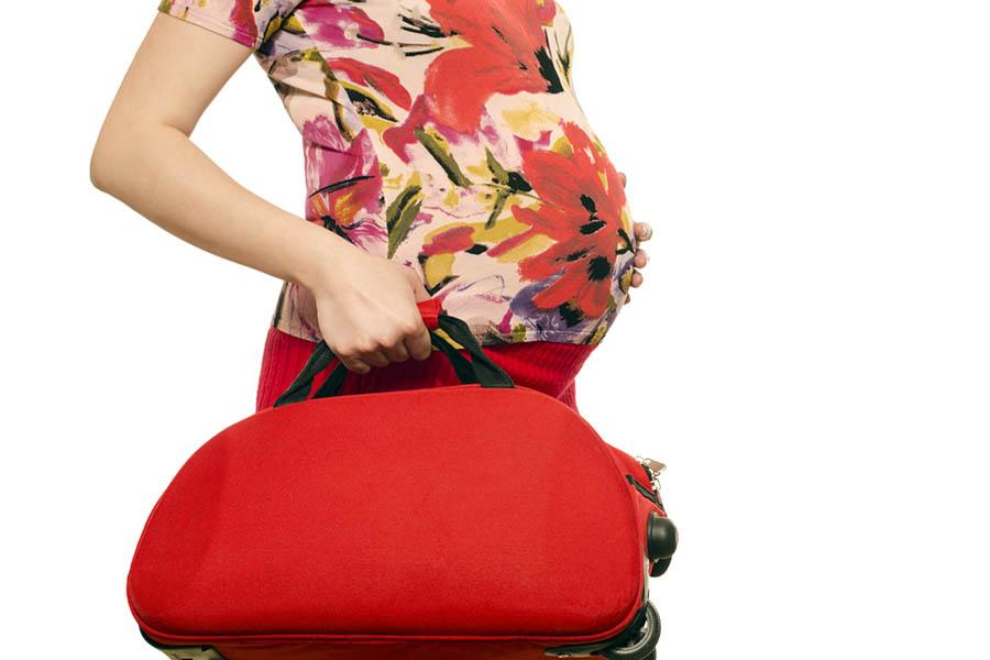 Zwangere vrouw met haar ziekenhuistas