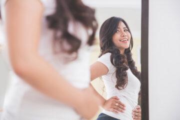 Zwanger of niet? vraagt vrouw zich af voor de spiegel