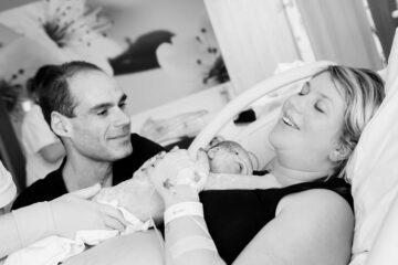 Partner heeft vrouw ondersteund tijdens bevalling en zit nu naast pasgeboren baby en vrouw