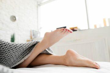De rusteloze benen van een vrouw op bed tijdens zwangerschap