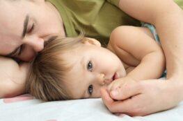 Vader ligt met baby na koortsstuip