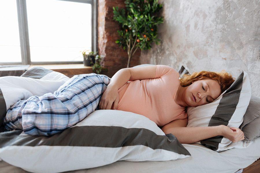 Zwangere vrouw ligt op bed met griep tijdens de zwangerschap