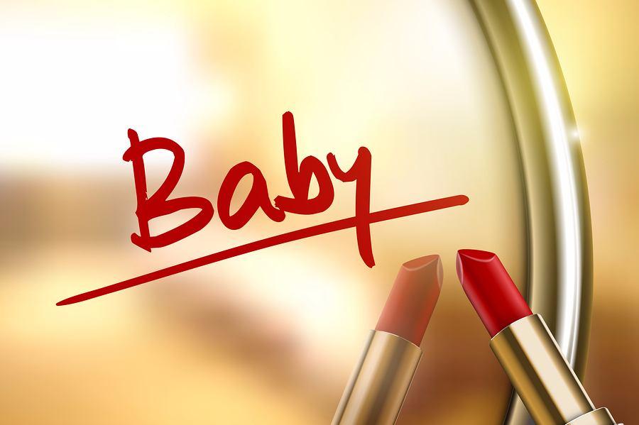 Het woord baby met lippenstift geschreven op spiegel