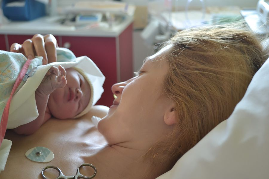 vrouw met baby na uitscheuren bevalling