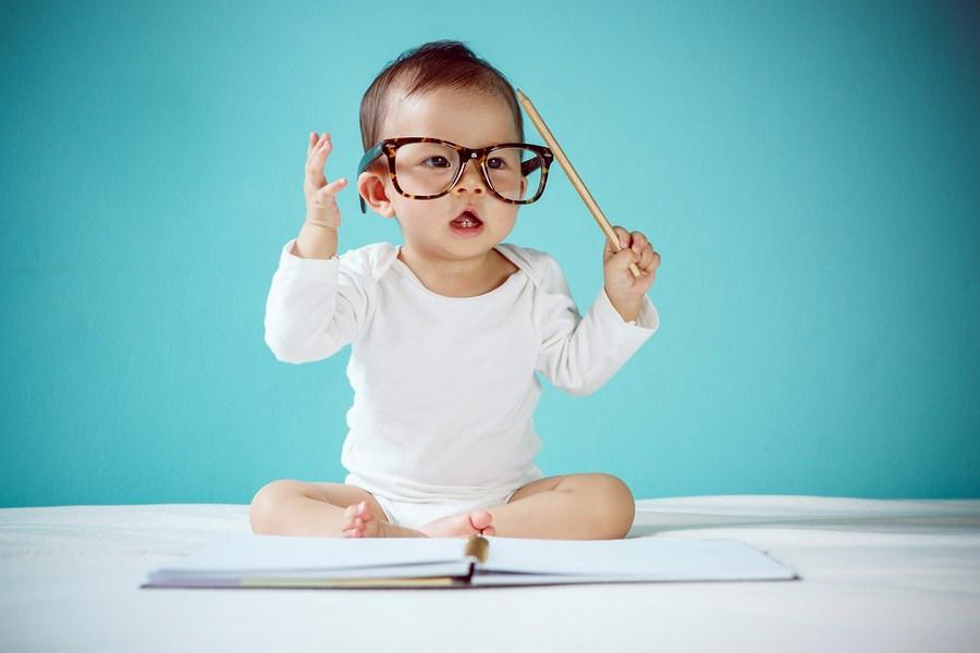Slimme aziatische baby met bril, potlood en boek