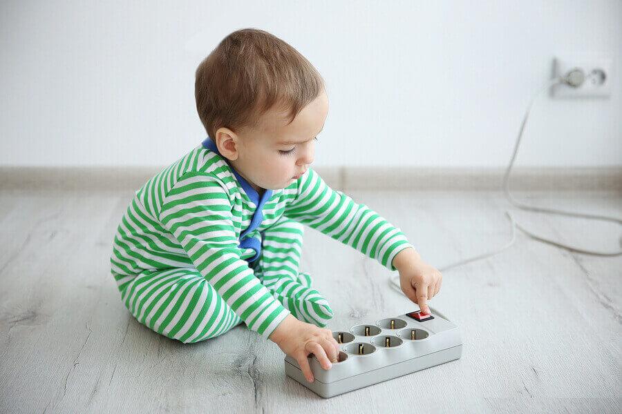 Baby speelt met stekkerdoos