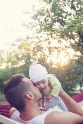 Vader geeft baby liefdevol een kus, buiten
