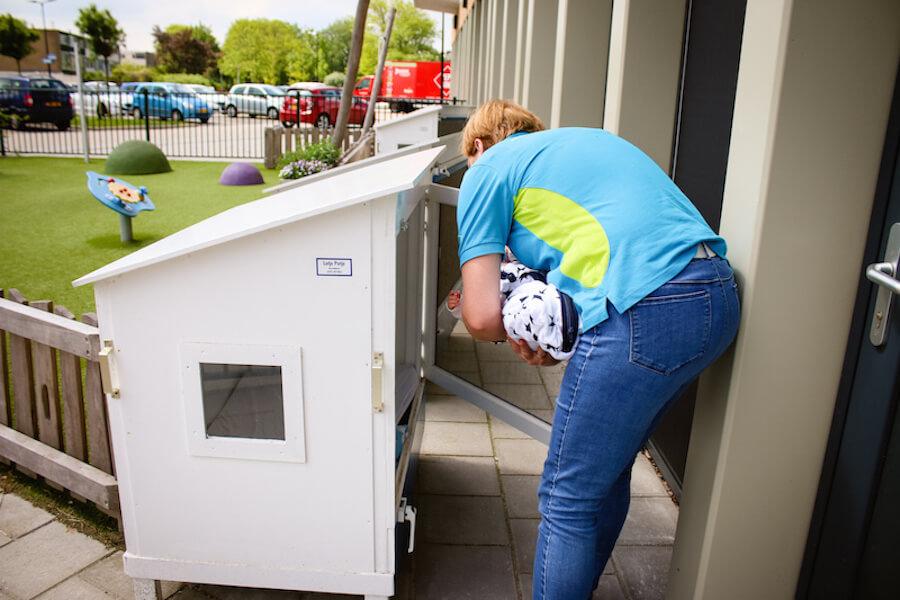 Pedagogisch medewerkster legt baby in buitenslaaphuisje