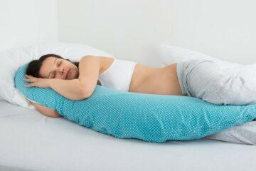 Een zwangere vrouw die op bed slaapt met haar voedingskussen
