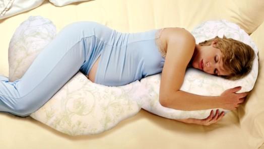 Vrouw die slaapt op een C-vorm voedingskussen