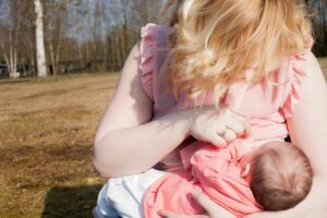 Vrouw geeft baby borstvoeding in het openbaar