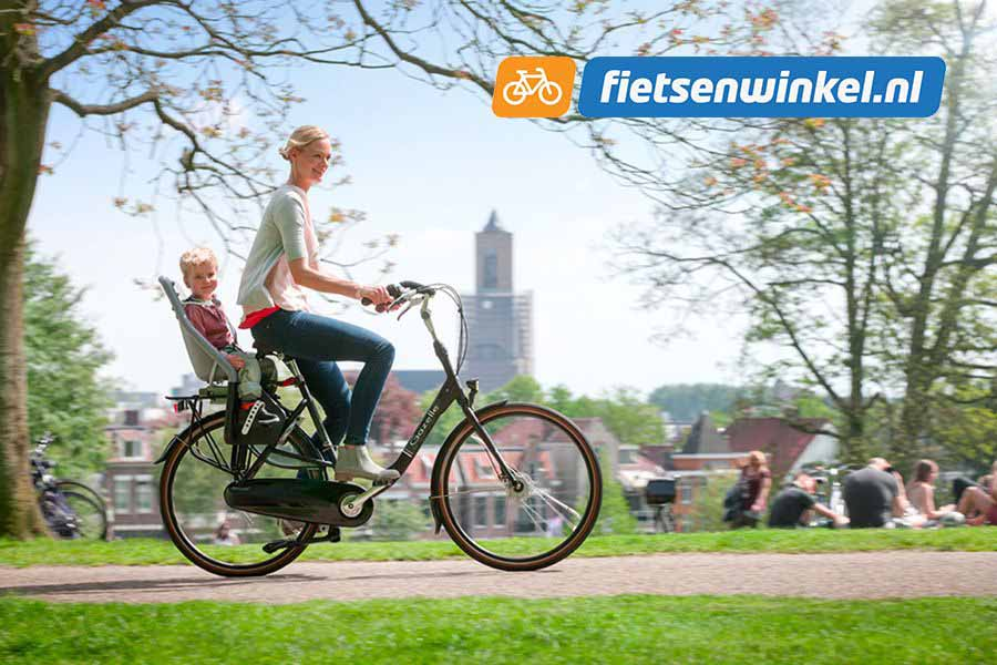 moeder fietst op moederfiets met kindje achterop