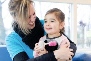 Kinderdagverblijf medewerkster lachend met baby