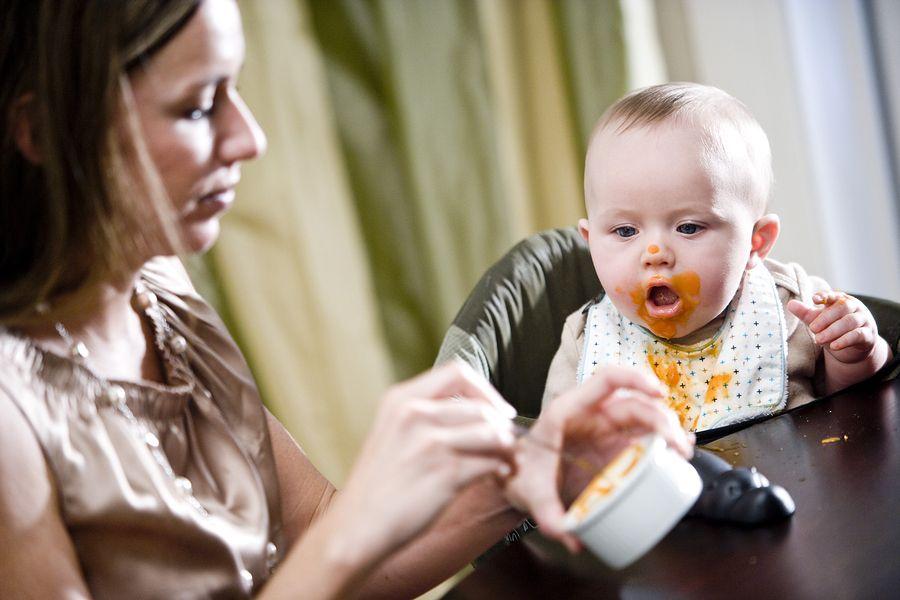 Moeder voert haar baby eerste hapjes