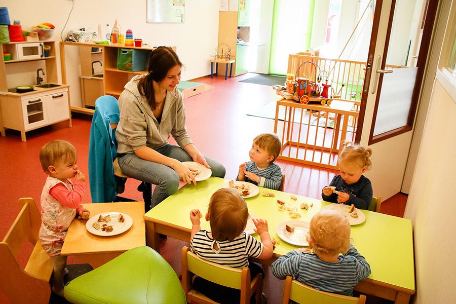 leidster en kinderen eten bij kinderdagverblijf