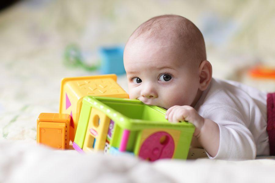 Baby van 10 weken oud stopt speelgoed in zijn mond