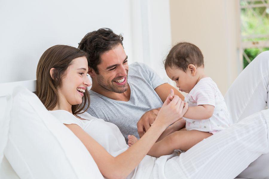 vrolijke-vader-en-moeder-met-baby-gaan-sparen-voor-baby