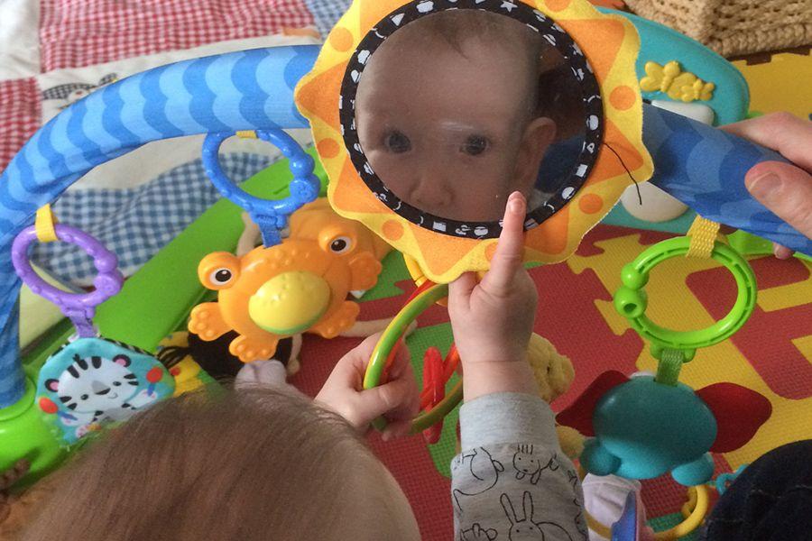 Baby van 15 weken oud kijkt naar zichzelf in spiegel