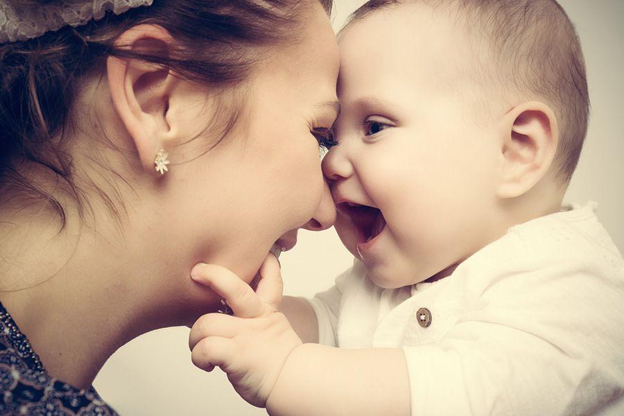 Moeder en baby van 15 weken oud zijn blij dat ze elkaar weer zien en lachen met de hoofden bij elkaar