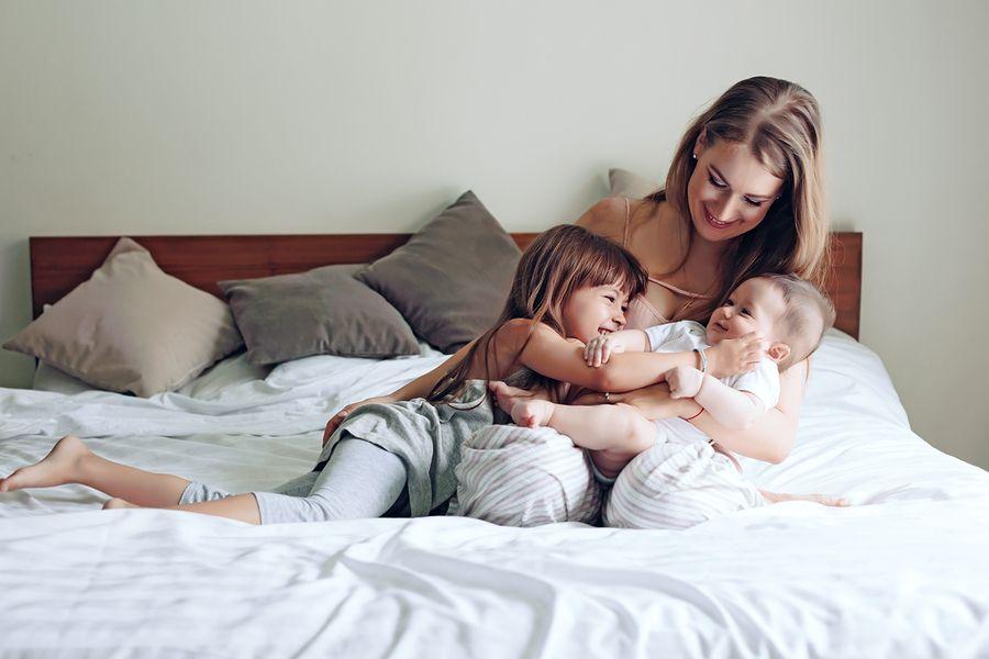 Moeder met 18 weken oude baby en peuterkindje op bed