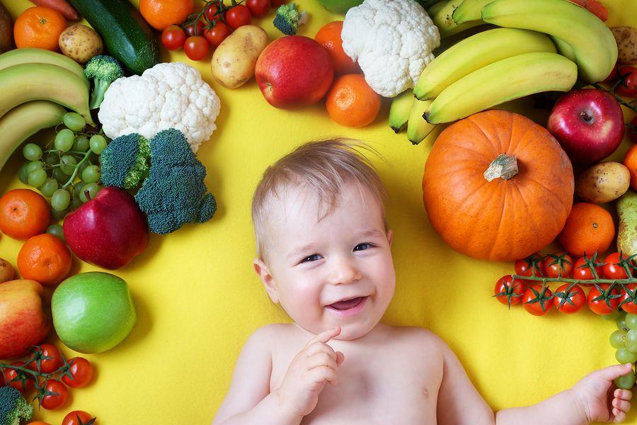 Baby-van-20-weken-oud-ligt-tussen-allerlei-verschillende-soorten-groente-en-fruit