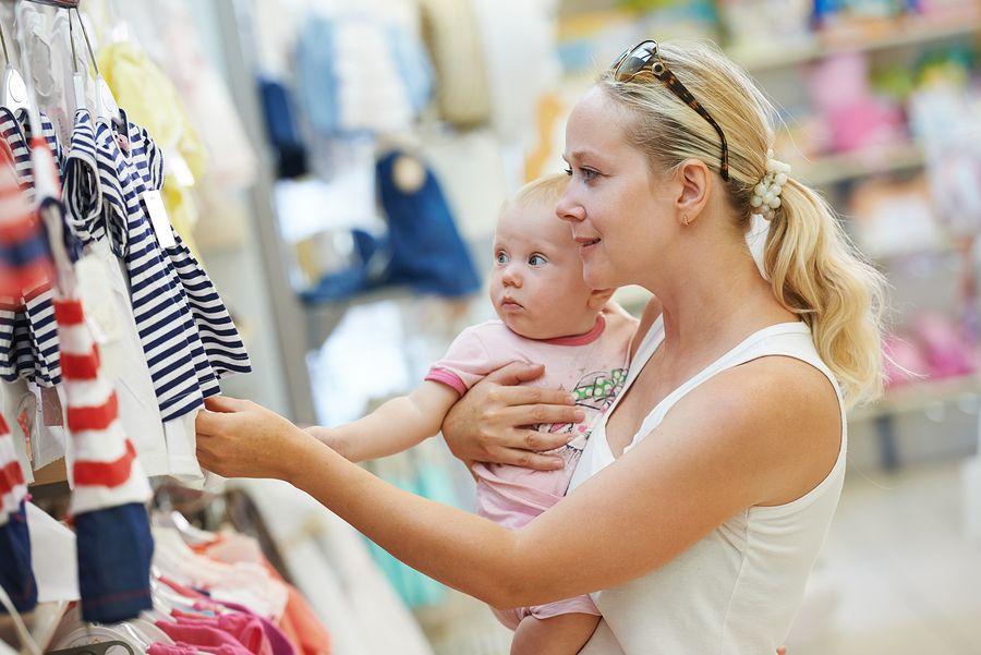 Moeder is kleding aan het kopen voor baby van 20 weken oud