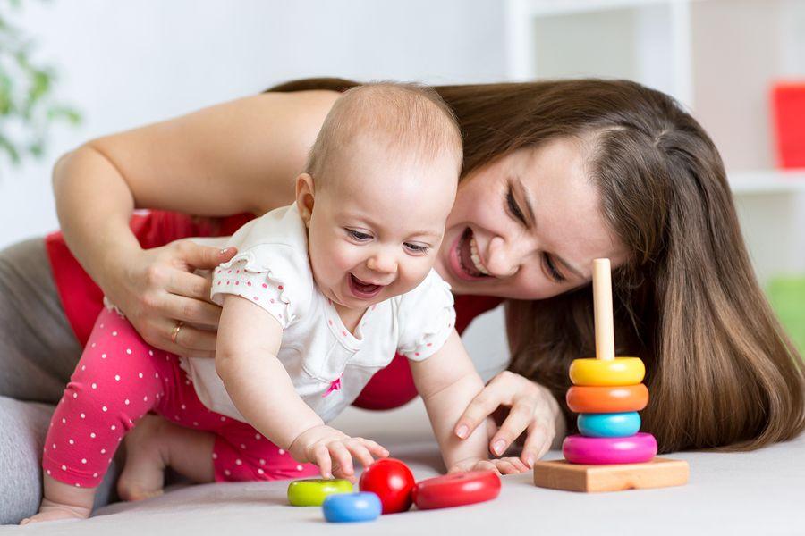 Moeder-en-baby-van-23-weken-oud-lachen-samen-en-baby-grijpt-naar-speelgoed