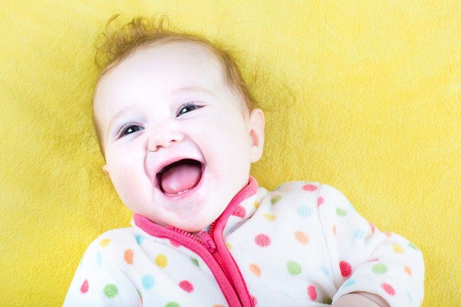 Lachende baby van 24 weken oud op gele achtergrond