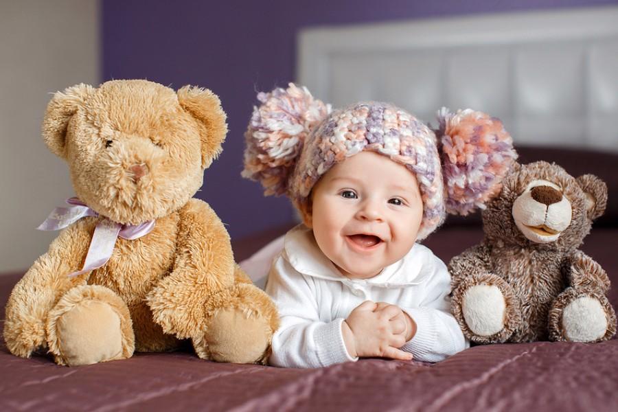 Lachende baby van 25 weken oud zit tussen twee knuffels in